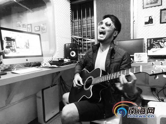 唐强在他的工作室里给记者弹唱《海口海口》