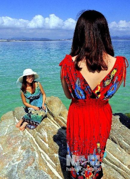 12月1日,在三亚市海边的一块礁石上,一位女游客摆出姿势让同伴拍照。