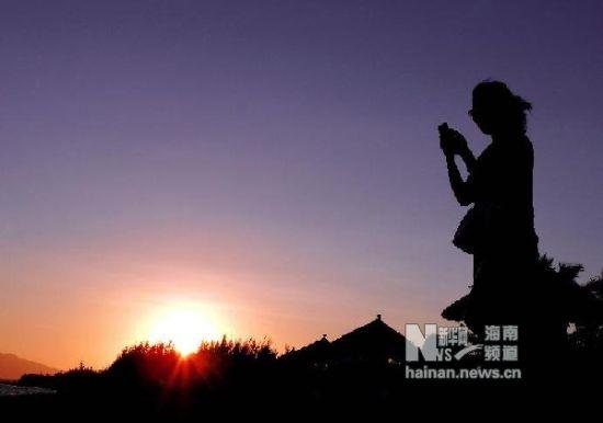 12月1日,在三亚市一处海水浴场附近,一位女游客在拍摄海景。