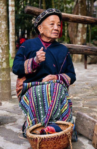 槟榔谷中一位伸手致意的黎族阿婆。小碎花装饰的头巾,银耳环边上巨大的耳洞,正在挑绣的黎锦,以及脸上一道道代表部落符号的文身,她身上有着太多作为黎族人的印记