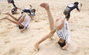 小队员要在沙滩边翻跟头,这种动作是冲浪的重要内容。