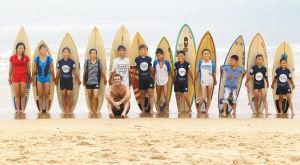 """万宁市冲浪先锋队的12名孩子在自己的冲浪板前合影。法国人""""豆腐""""(前排)是他们的外籍教练。"""