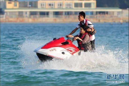 游客乘坐摩托艇游玩。与寒冷的北方相比,正值旅游旺季的海南三亚气候依然如夏。众多游客在三亚海边戏水、晒日光浴,享受着天涯海角的独特气候。 新华社记者 侯建森摄