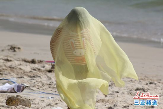 一小孩在用围巾遮阳