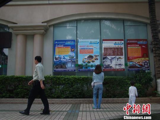 图为游客在海南奥林匹克国旅外墙上看旅游线路宣传栏。 琼芬 摄
