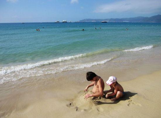 看小妹妹正在帮助小哥哥堆沙