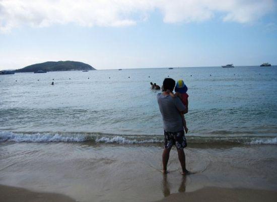 逆光中的父女俩,小女孩也许是第一次与大海亲密接触?