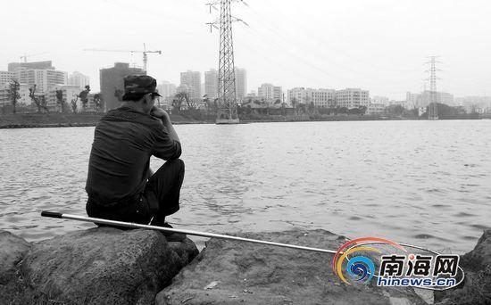 在红城湖边,一位市民拿着渔网在岸边等着捞鱼(摄于2013年3月6日)。南国都市报记者敖坤摄