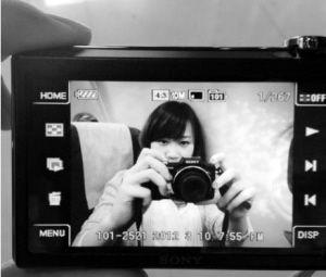 相机画面中一名年轻女子手拿着相机。图片来源网友微博