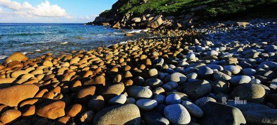 海滩上堆积着层层叠叠、密密麻麻的卵石,色彩分明