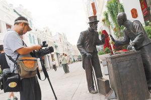 5月8日,在海口市中山路骑楼,美国探索发现频道摄制组的摄像师正在拍摄纪录骑楼文化。 海南日报记者 张杰 摄