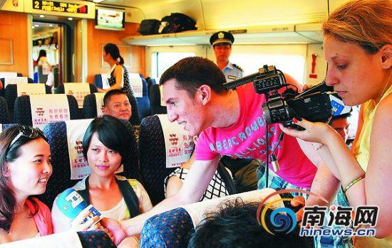 """5月22日,参加""""外媒看海南""""采风活动的外国媒体记者在东环高铁动车上采访。"""