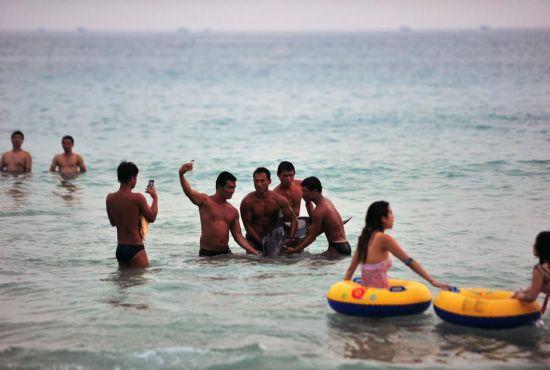 三亚市民游客将搁浅海豚抬出水面合影