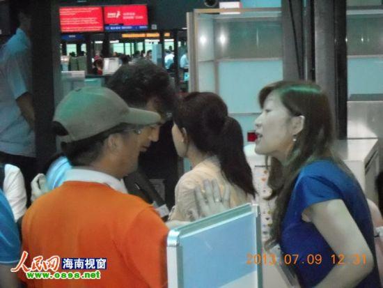 蓝衣女子(图右)在行李托运处大声骂人(图中低头者)
