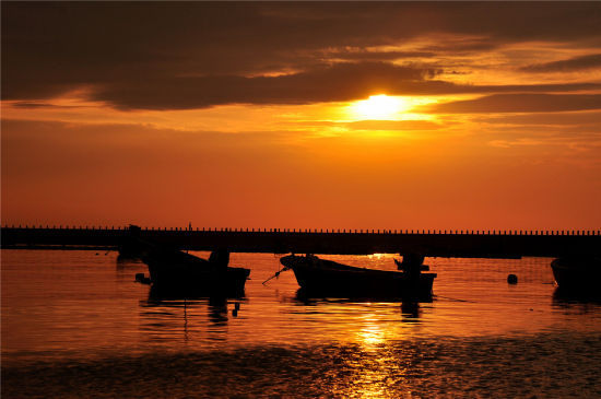 夕阳在港的那头正慢慢的下去,而夕阳的余辉正照在港中的每一处,构成了一幅漂亮的渔港夕阳图