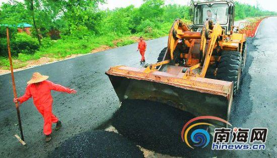 在文昌滨海旅游公路东龙段上,工人正在雨后加紧施工。