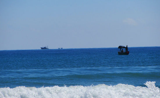 偶有几只船在宝石蓝的海水上