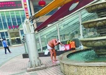 男子用喷泉洗澡