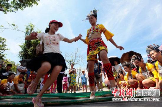 5月3日五一小长假第三天,游客和黎族姑娘在南山景区跳竹竿舞。陈文武 摄
