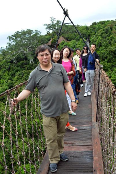 图为国旅总社考察团一行在景区过江龙索桥合影留念